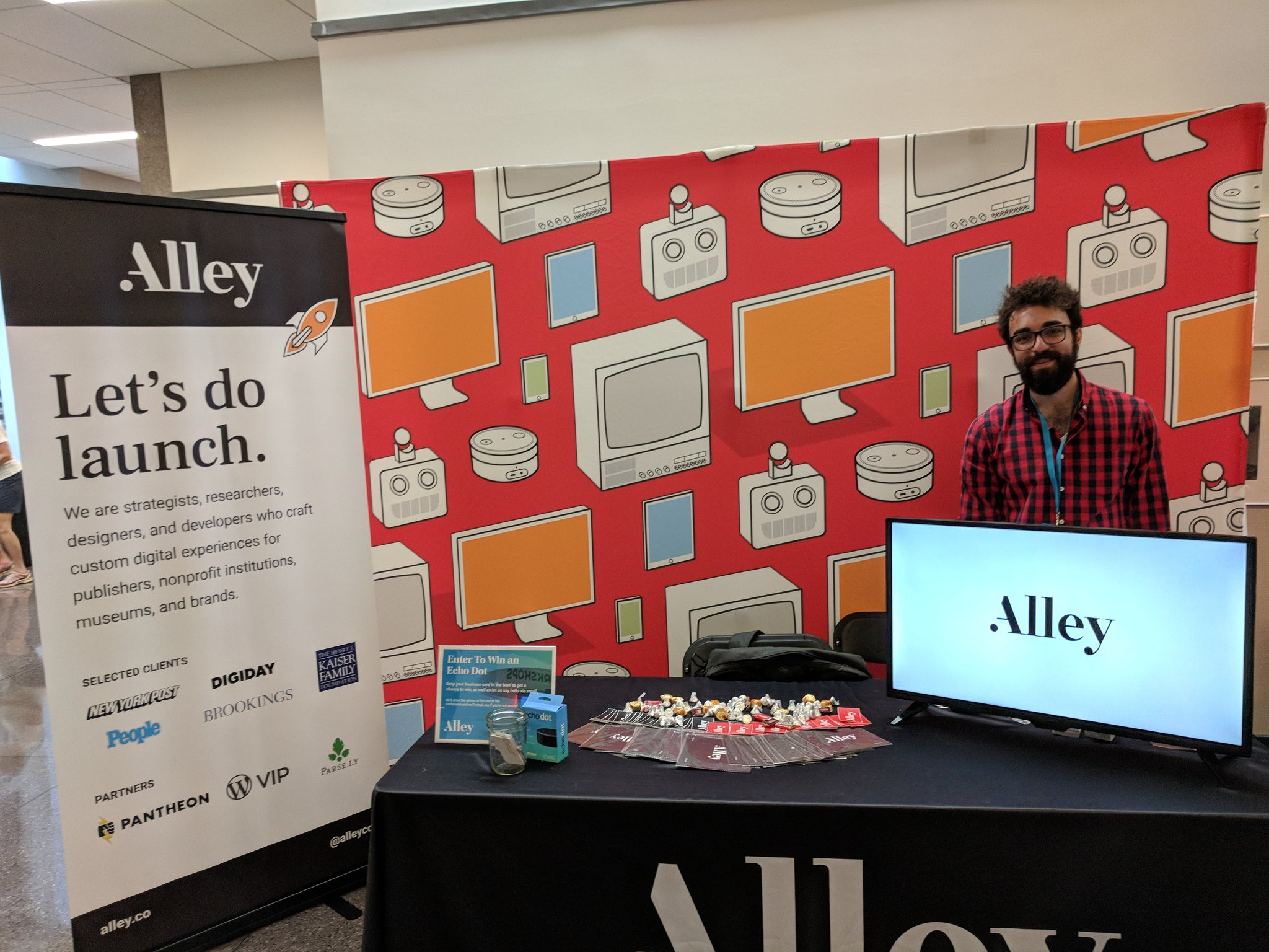 The Alley conference booth with a red  background with computers and tech devices, a television screen with the Alley logo, and a banner, as well as a White man in a plaid shirt smiling at the camera