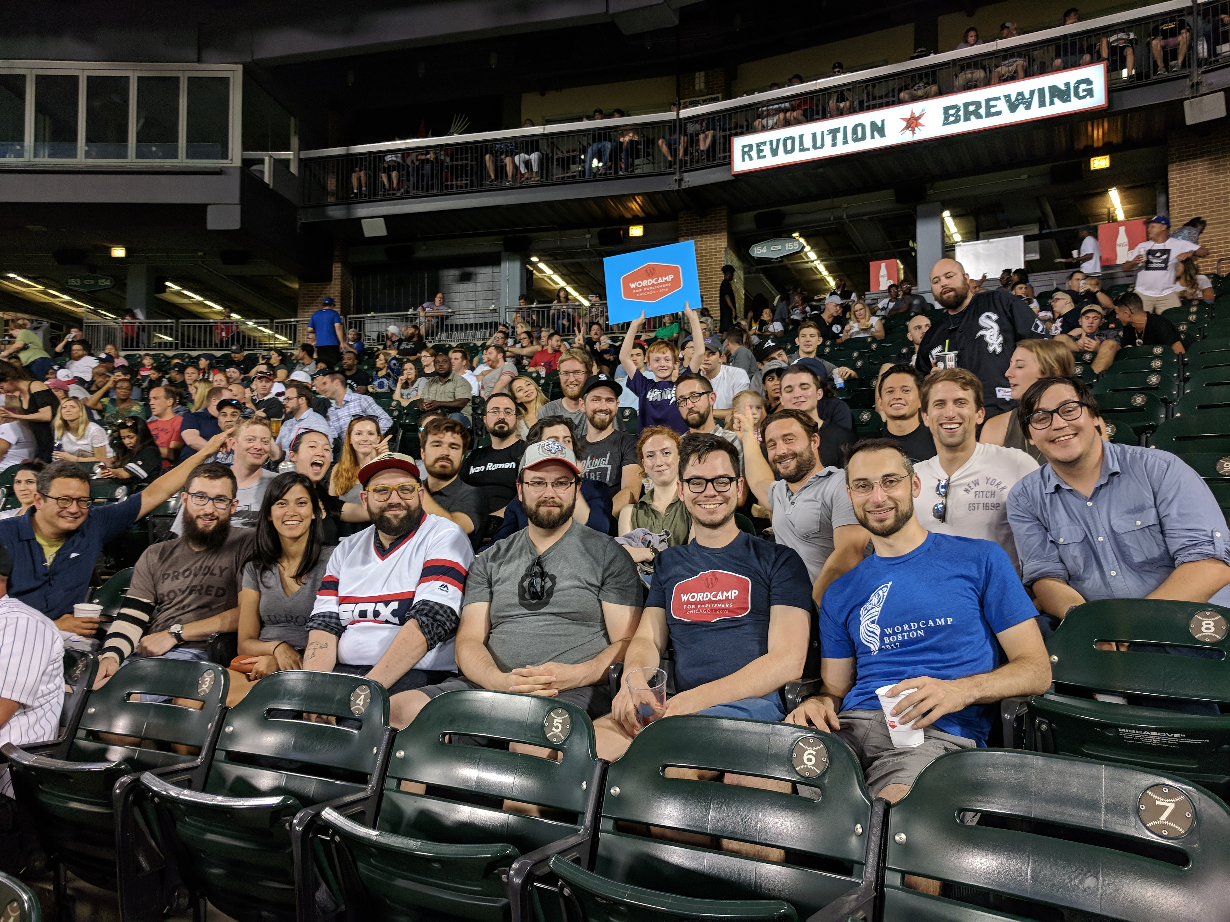 A group of people sitting in the stands of a baseball stadium