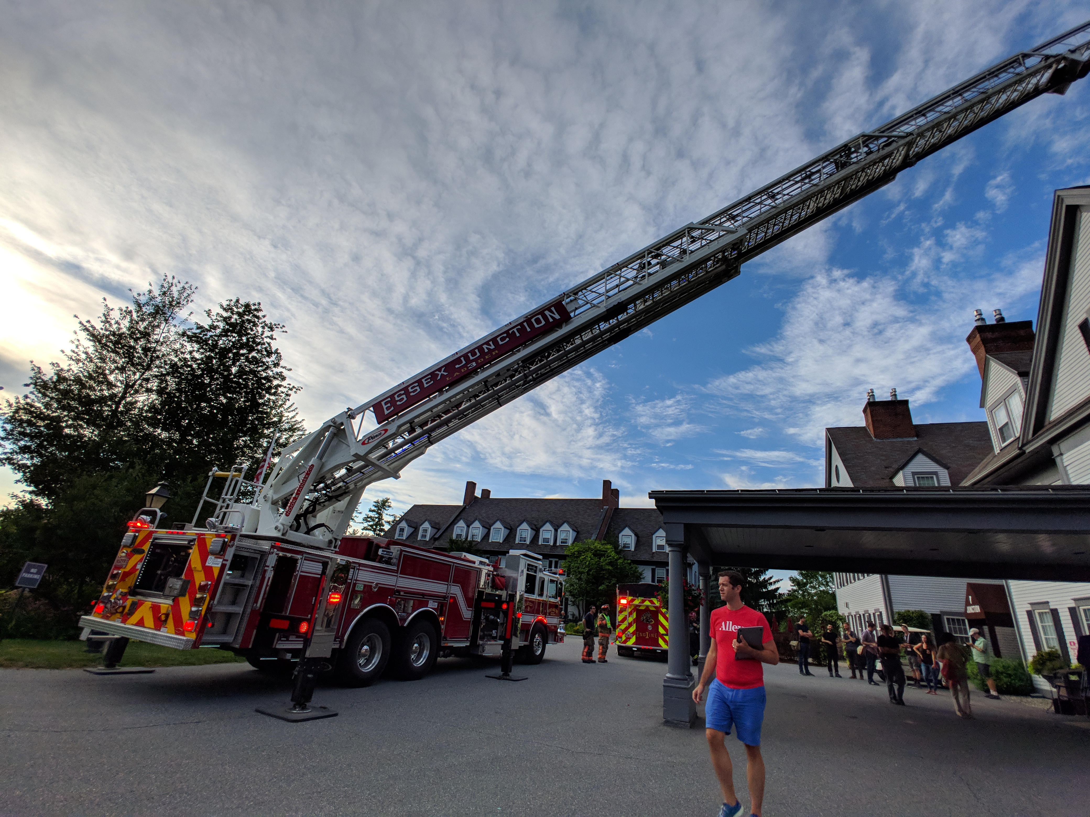 A fire truck with a long ladder fully extended to reach the top of the building next door while a White man with a red Alley shirt and blue shorts walks in front