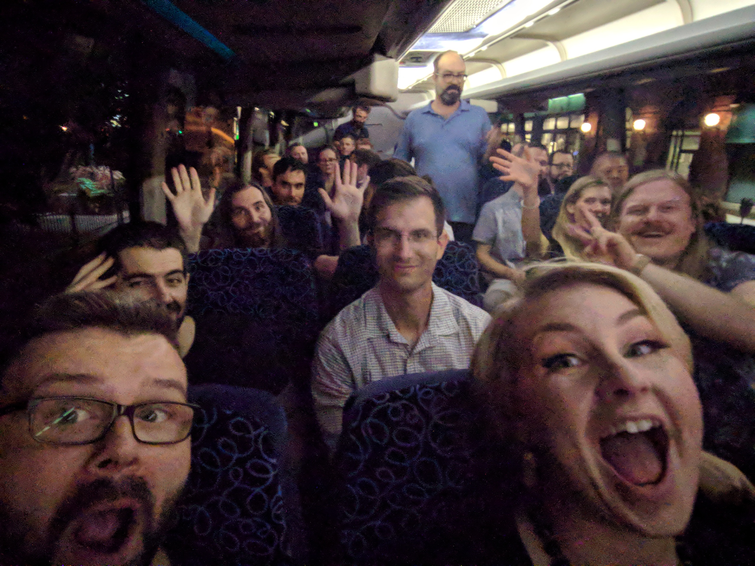 A selfie of many team members on a bus smiling and waving their hands