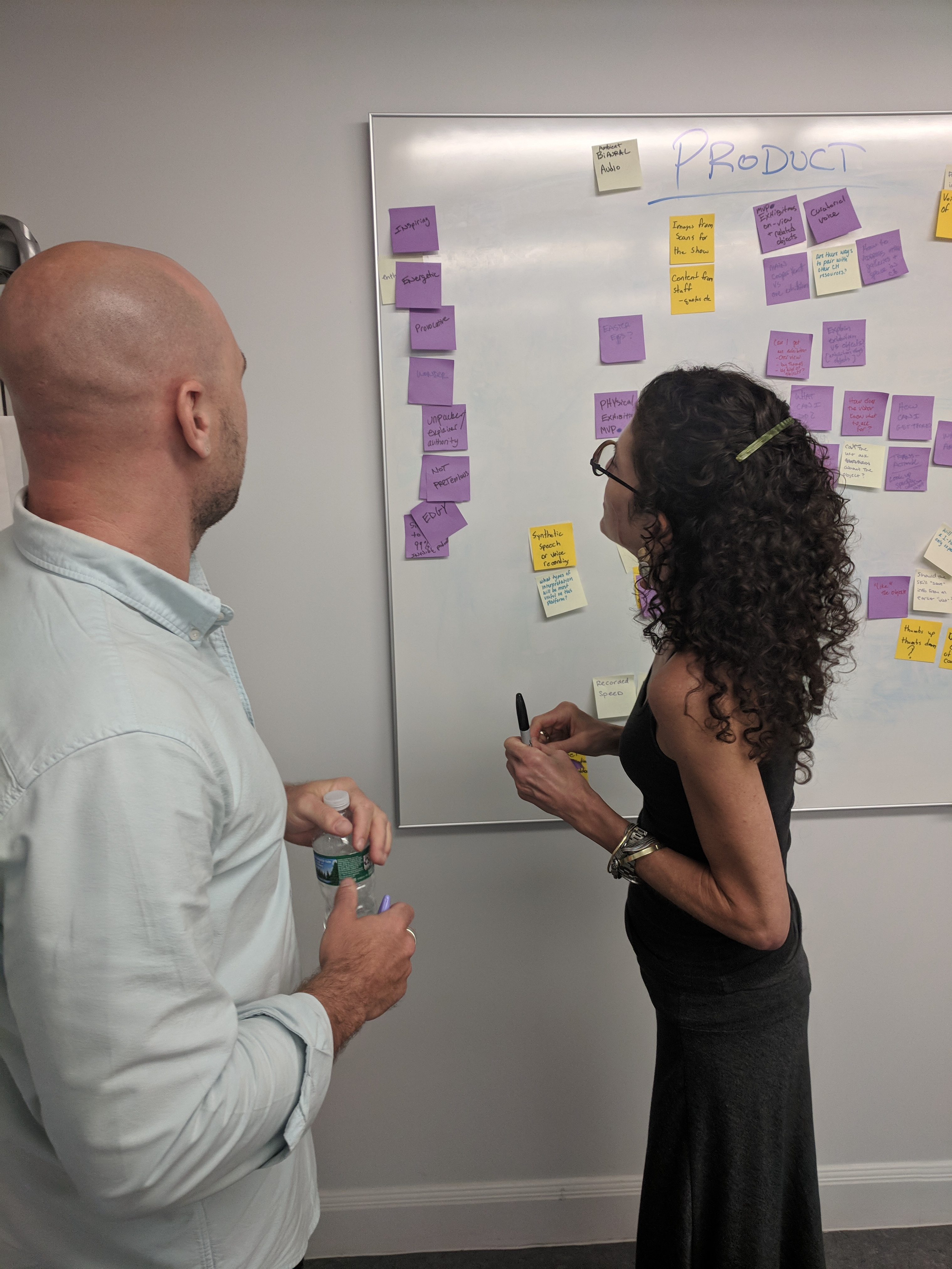 Two people standing at a white board looking at a string of purple post its