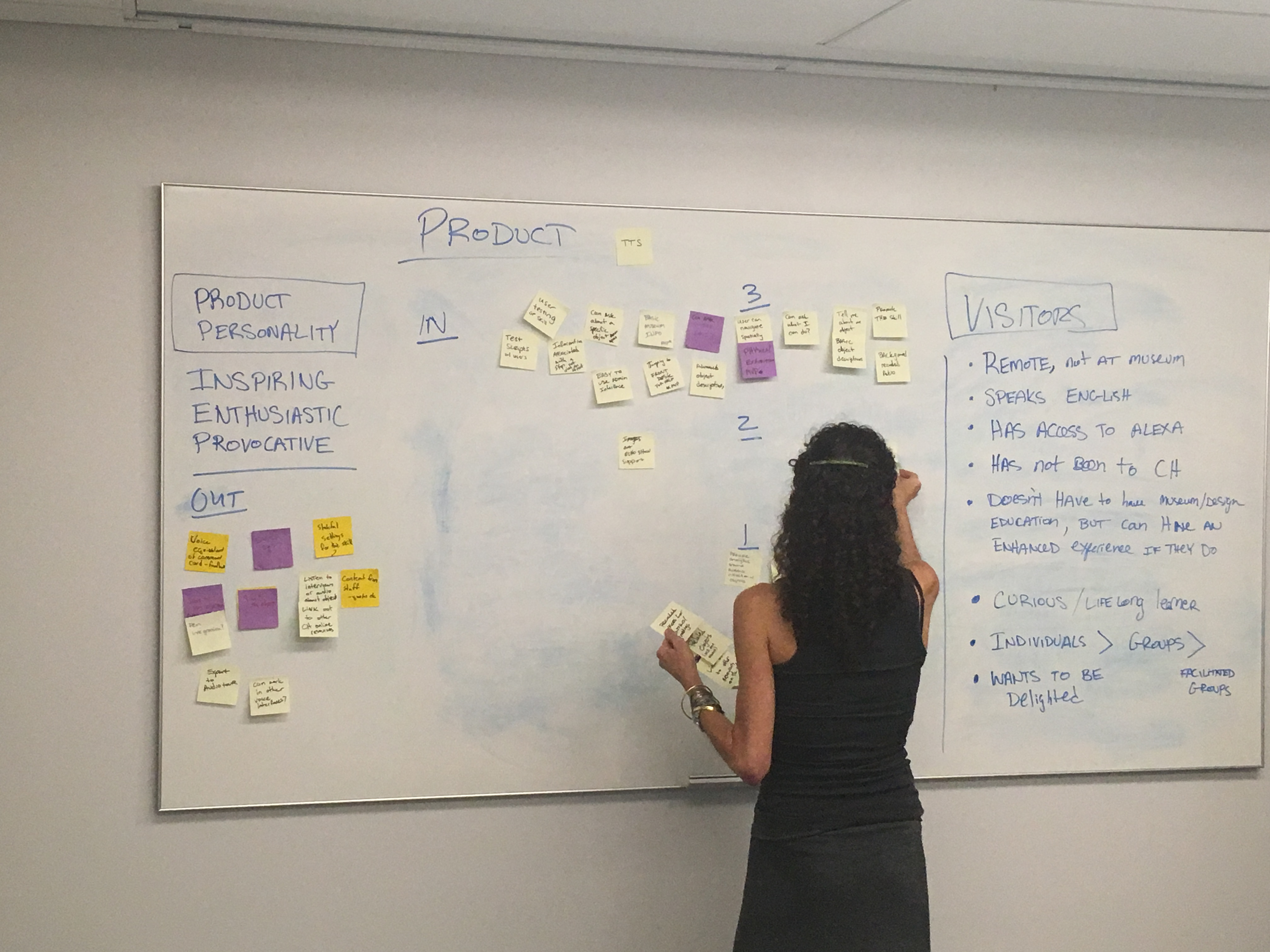 A woman adding post its to a white board with a lot of information on it
