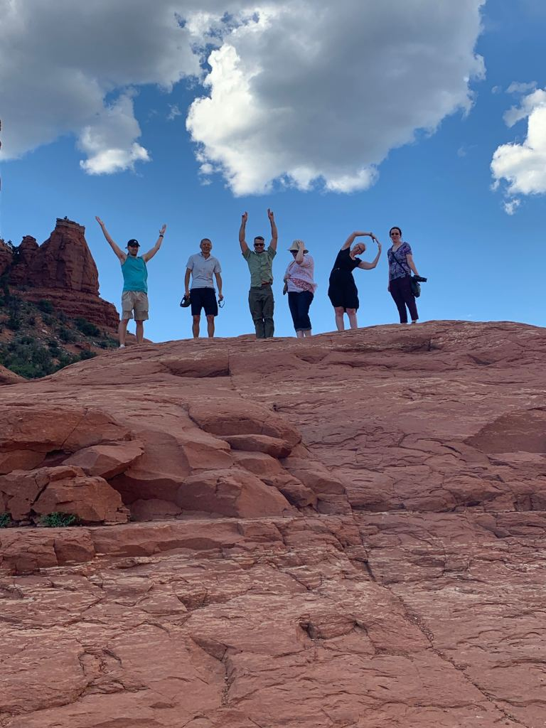 "The team stands on top of a large red rock and attempt to spell out ""VIP"" with their bodies."