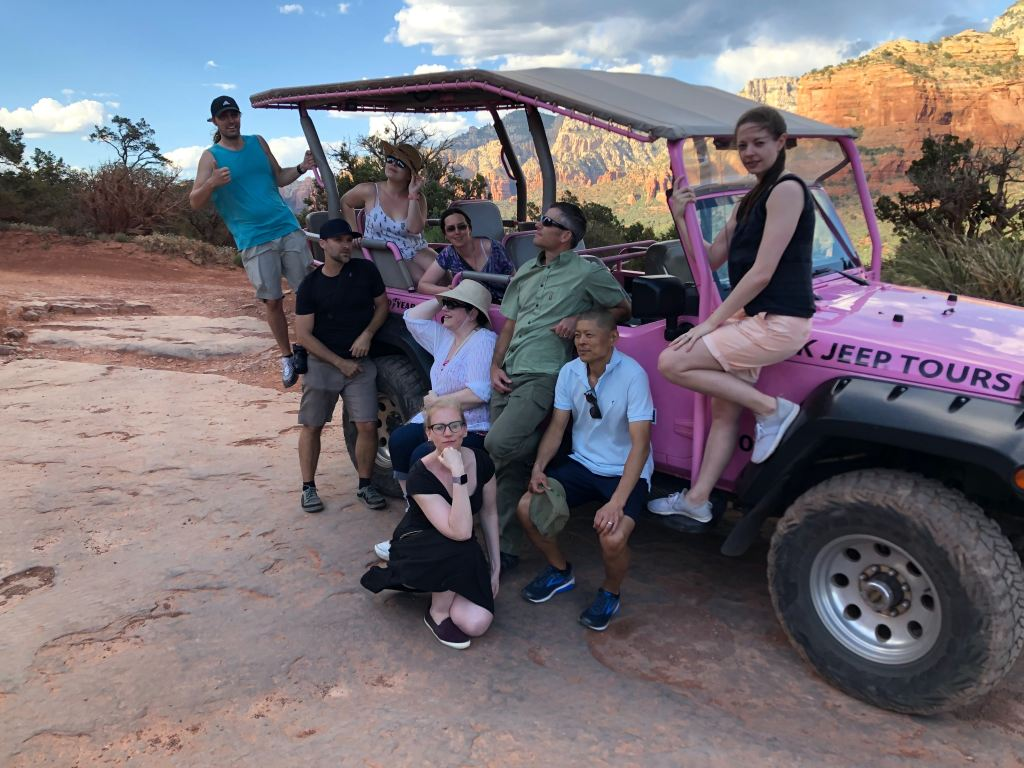 The team posing around their pink jeep after a tour of Sedona hiking trails.