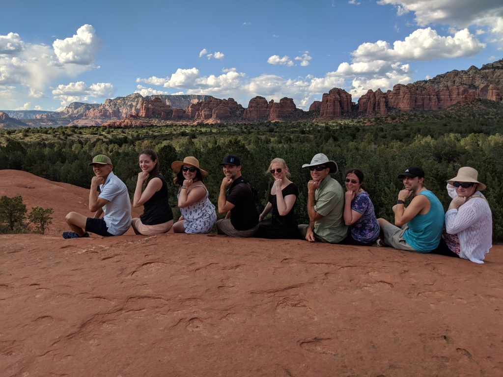 Team VIP sitting in a row all holding the same pose with their fists under their chins as though pondering something. Backdrop against the red rocks at Sedona