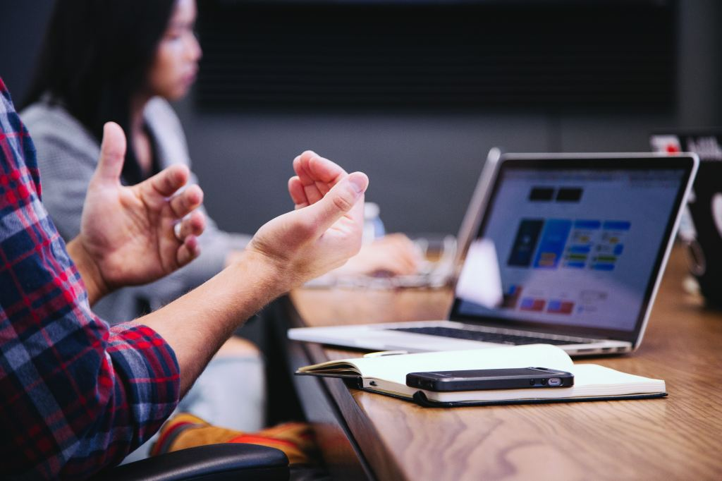 People gesturing in front of a computer in a meeting that matters