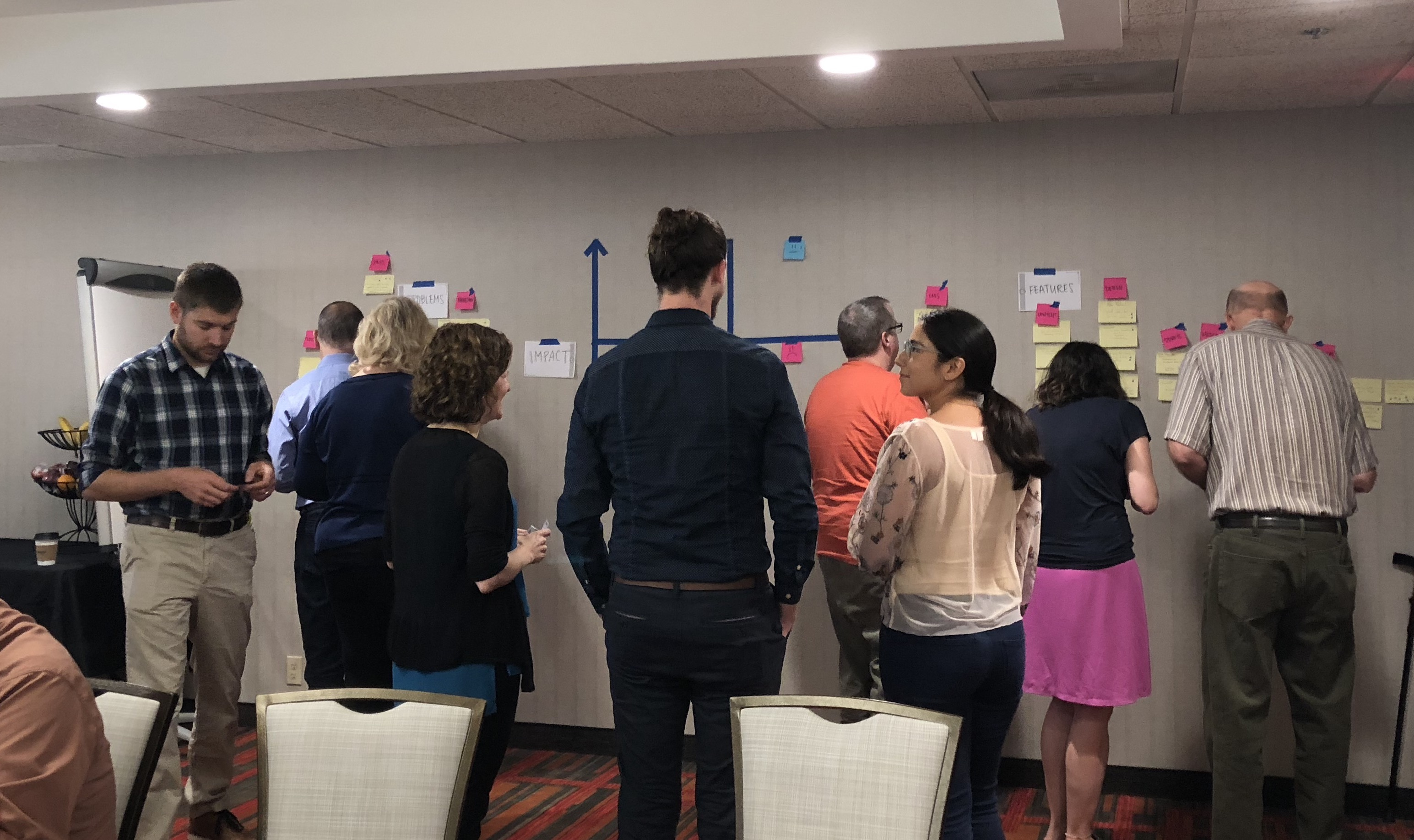 A large group of people looking at a display of post its and tape on the wall of a conference room