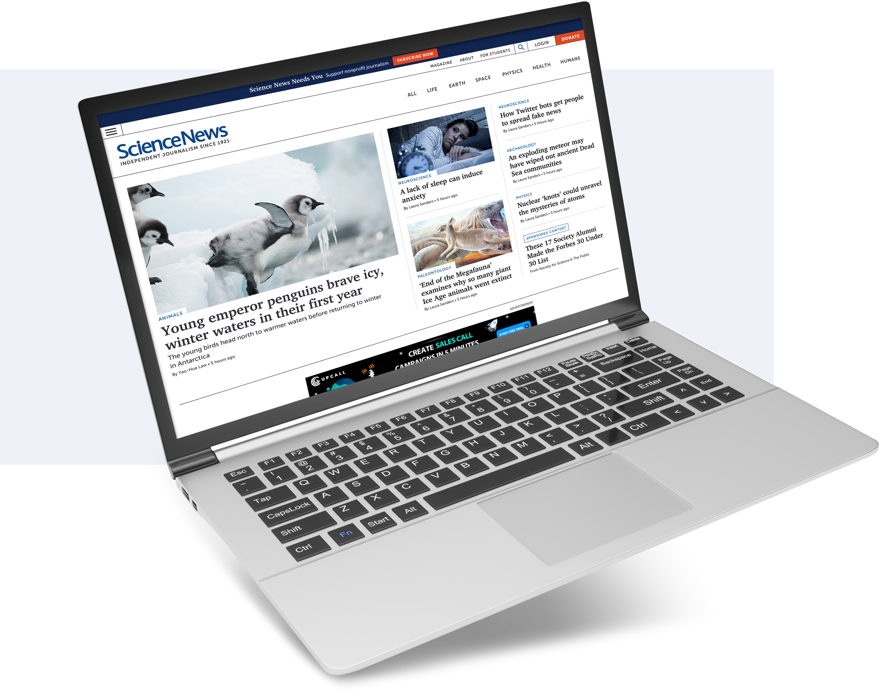 The main page of Science News with navigation, featured article, and additional content displayed on a laptop screen