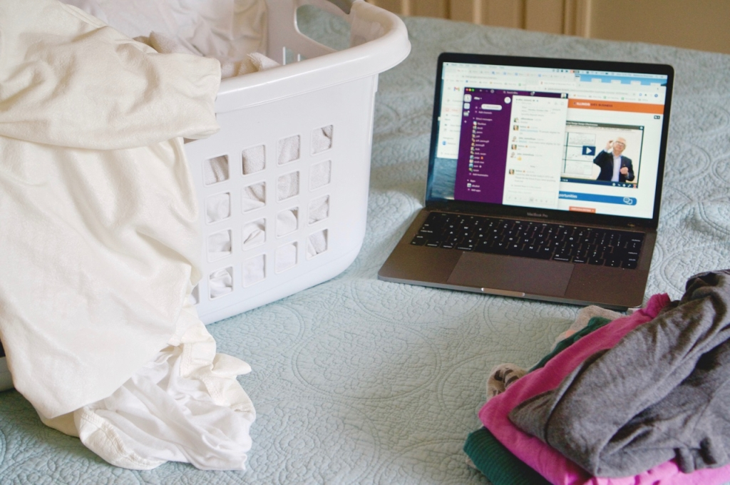 Laptop on bed with laundry basket beside it