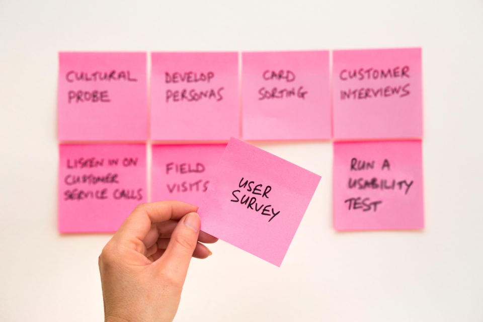 """A group of post-its on the wall, with a hand pulling off one that says """"User Survey"""""""