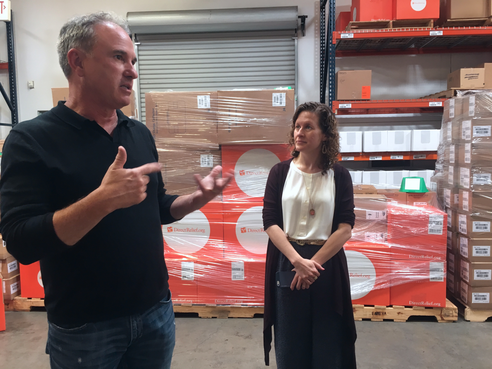 A woman listening to a gesturing man in a large warehouse in front of many shrinkwrapped orange boxes with the Direct Relief logo on them