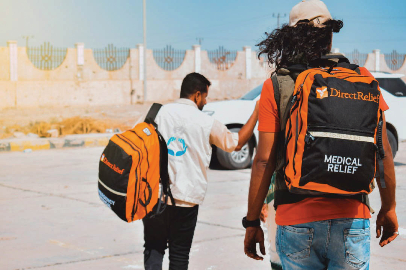 Two men with their back to the camera with orange and black Direct Relief backpacks on