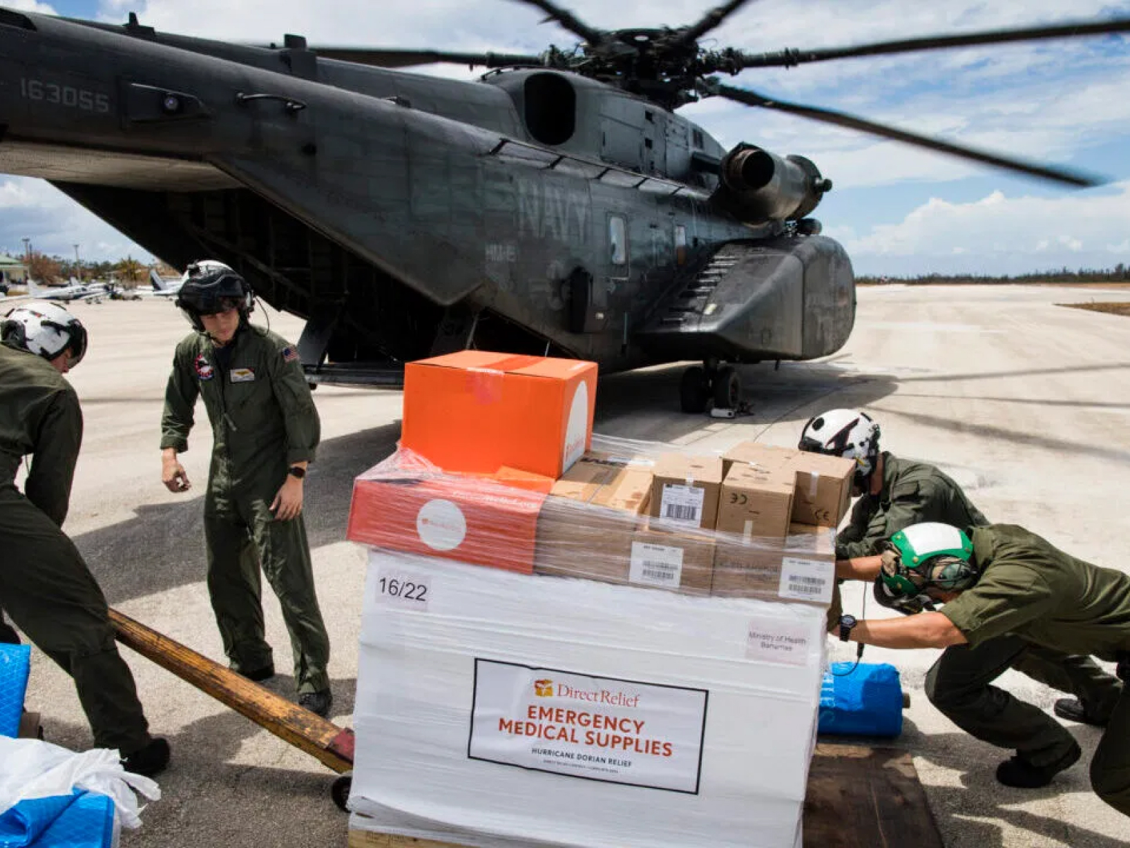 Four men in helmets pushing a pallet labelled emergency medical supplies into a large black Navy helicopter